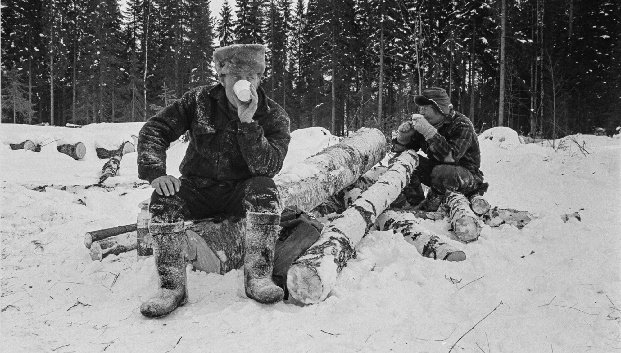 Kaksi metsätyöntekijää lumisissa vaatteissa pitämässä taukoa tukkien päällä ja juomassa kahvia.