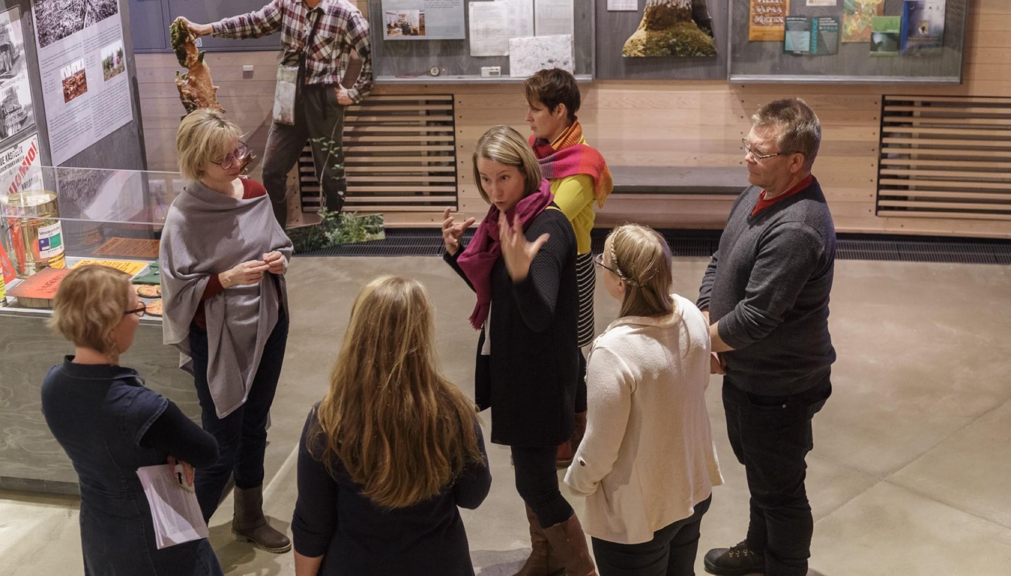 Ryhmä ihmisiä Lustossa, keskellä opas selittää ilmeikkäästi.