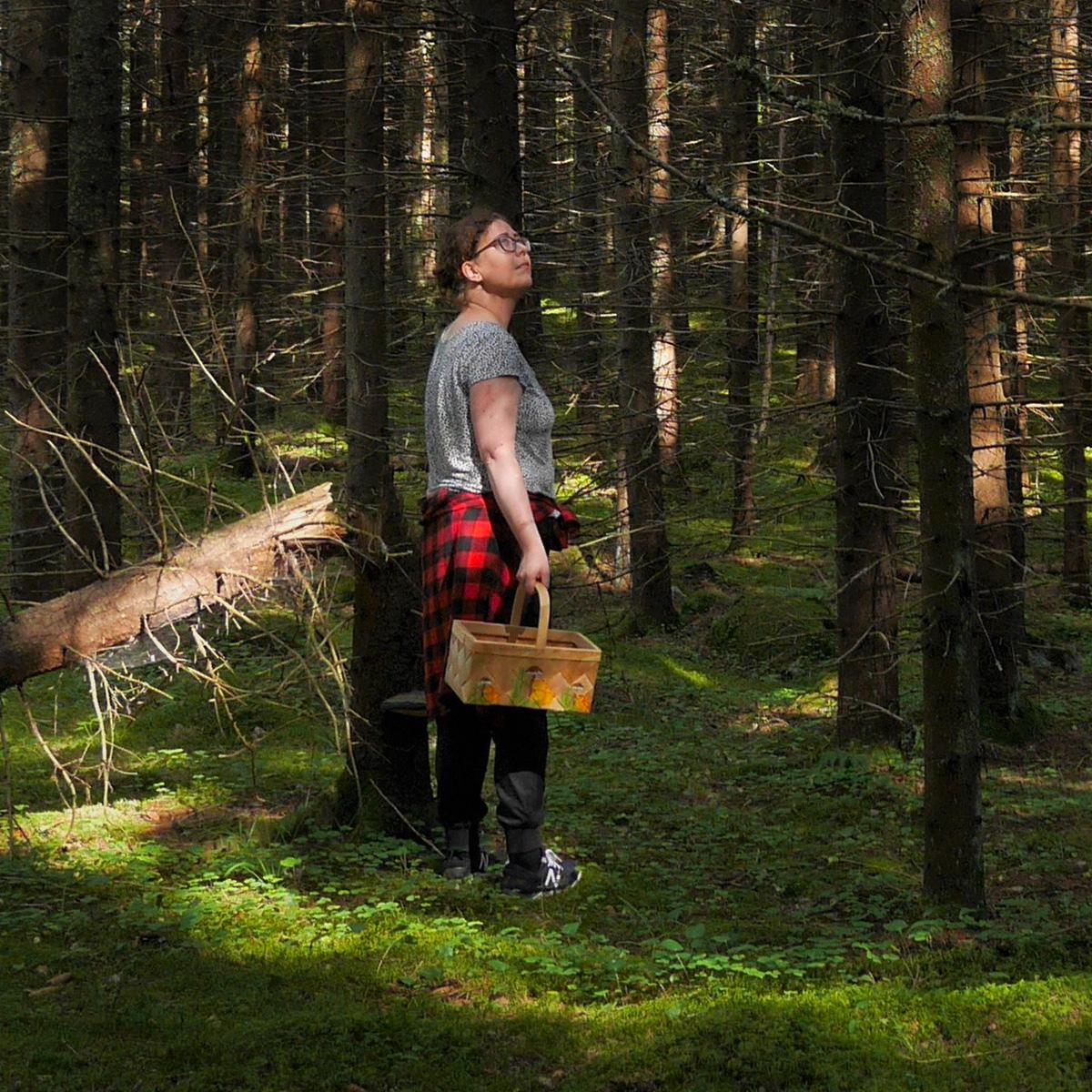 Nainen t-paidassa ja sienikori kädessä hämyisessä metsässä.