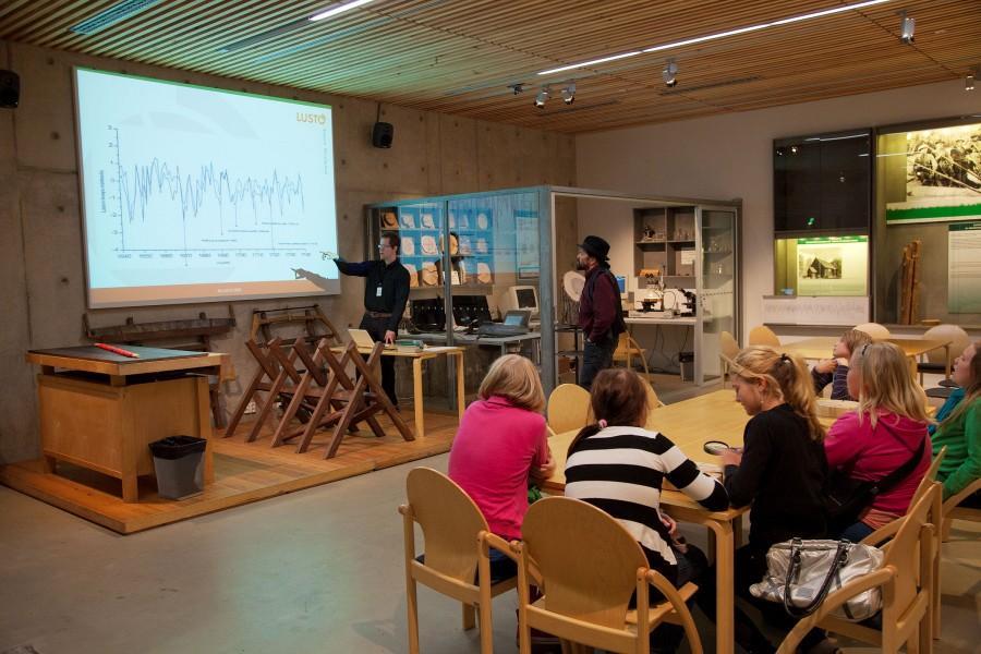 Ryhmä ihmisiä työskentelee pöydän ääressä etualalla, taustalla mies osoittaa kankaalle heijastettua graafia.