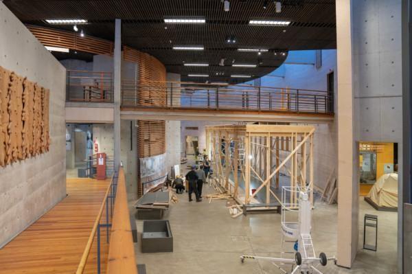 Joukko miehiä purkamassa puista rakennetta näyttelytilasta. Rakenteesta on enää runko jäljellä.