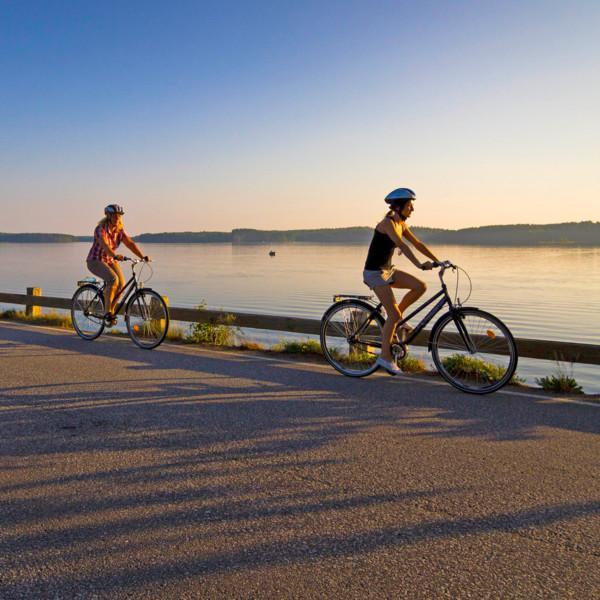 Kaksi pyörälijää ilta-auringossa maantiesillalla, takanaan peilityyni järvi.