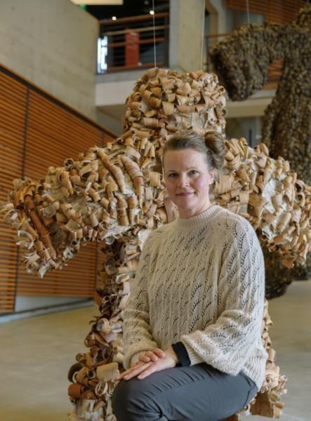 Jenni Tieaho näyttelytilassa, taustalla tuohesta tehty takki.