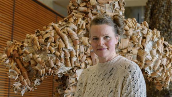 Jenni Tieaho, taustalla tuohesta tehty takki.