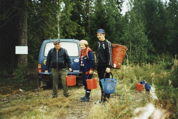 Kolme marjanpoimijaa metsässä sankojen kanssa, taustalla pakettiauto.