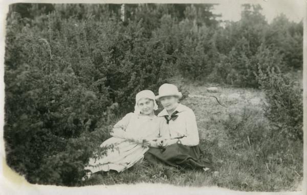 Mustavalkokuvassa naiset istuvat maassa katajien keskellä.