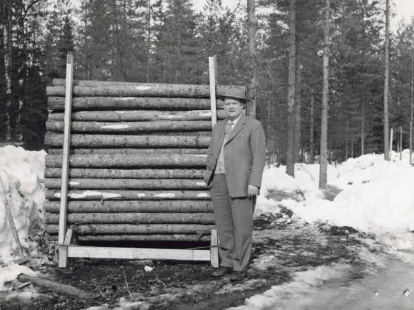 Mustavalkoisessa kuvassa mies seisoo itsensä korkuisen propsipinon vieressä.