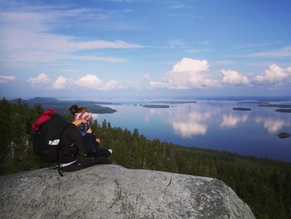 Etualalla nainen istuu kalliolla lapsi sylissään taustalla maisema Kolilta, metsää ja järvi.