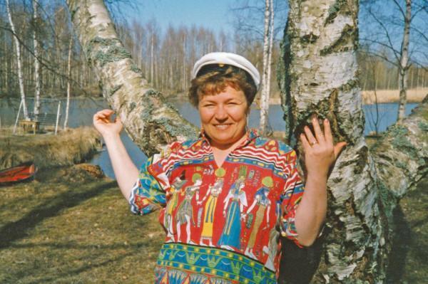Etualalla nainen ylioppilaslaki päässä, taustalla haaroittuva koivu, nurma ja järvi.