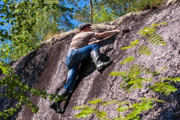 Mies kiipeää kalliolla, taustalla sininen taivas ja rehevää puustoa.