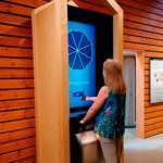 Nainen koskettamassa PuuSensei-laitetta Luston näyttelyssä.
